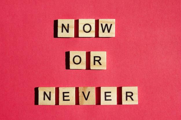Nu of nooit - houten blokken met zwarte letters. oproep tot actie. motivatie voor iedereen. Premium Foto