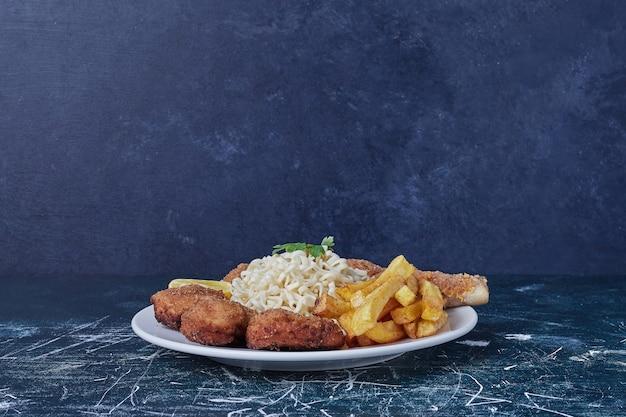 Nuggets met gebakken aardappelen en noedels. Gratis Foto
