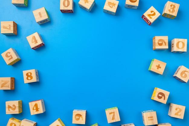 Numbers. de houten kleurrijke alfabetblokken op blauwe vlakke achtergrond, leggen, hoogste mening. Premium Foto