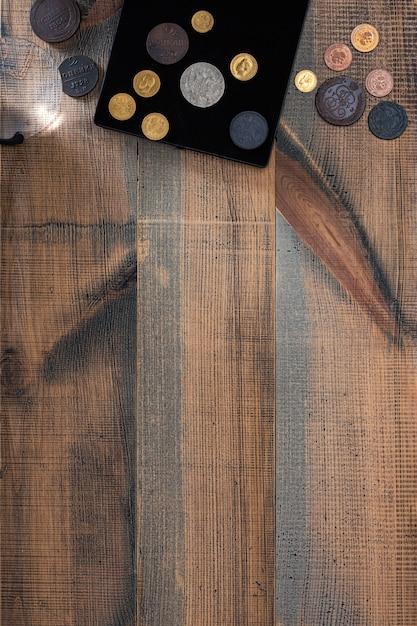 Numismatiek. oude collectible munten gemaakt van zilver, goud en koper op een houten tafel. bovenaanzicht. kopieer de ruimte van uw tekst. Premium Foto