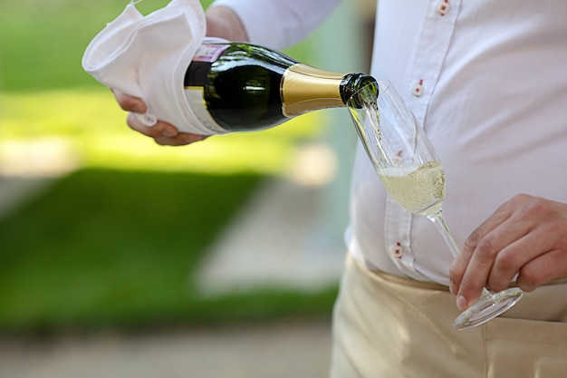 Ober gieten champagne in glas met dunne poot Premium Foto