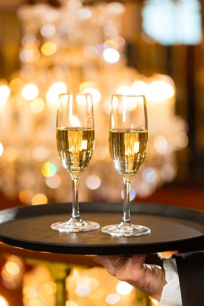 Ober serveerde champagneglazen op een dienblad in een gastronomisch restaurant, een grote kroonluchter is binnen Premium Foto