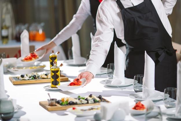 Ober serveertafel in het restaurant bereidt zich voor om gasten te ontvangen. Premium Foto