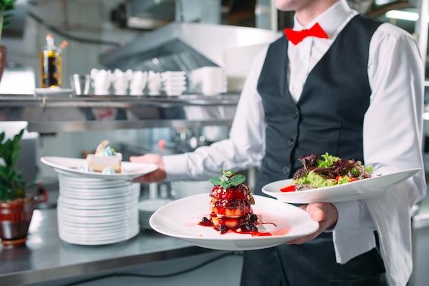 Ober serveren in beweging op plicht in restaurant. de ober draagt gerechten. Premium Foto