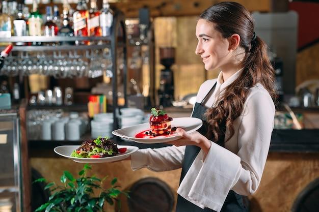 Ober serveren in beweging op plicht in restaurant. de ober draagt gerechten Premium Foto