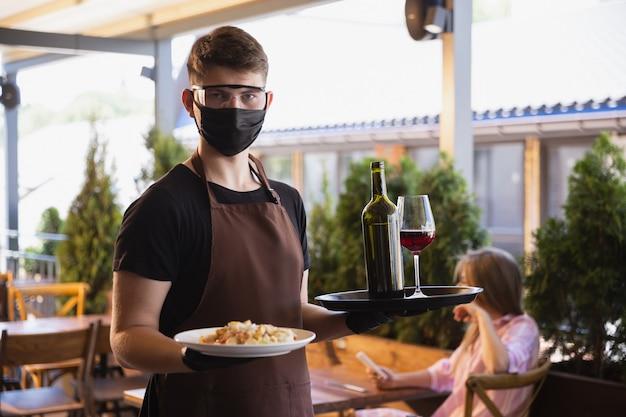 Ober werkt in een restaurant in een medisch masker, handschoenen tijdens pandemie van het coronavirus Gratis Foto