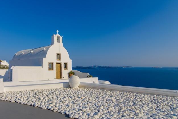 Observatiedek en hotelkamer met uitzicht op de zee en de stad oia, santorini. Premium Foto