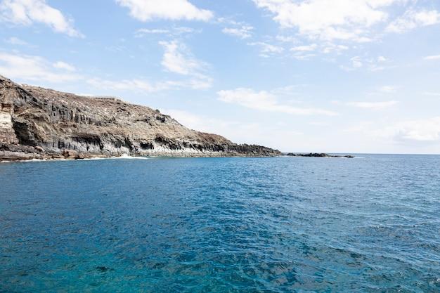 Oceaan kuststreek met klippen en bewolkte hemel Gratis Foto