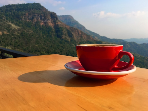 Ochtend hete latte kunstkoffie in een rode kop op houten balkon bij de helling Premium Foto