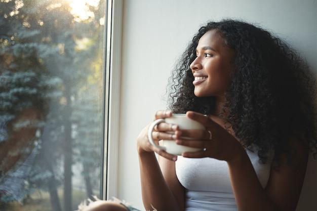 Ochtend routine. portret van gelukkig charmant jong gemengd ras vrouw met golvend haar genieten van zomer uitzicht door raam, goede koffie drinken, zittend op de vensterbank en glimlachen. mooie dagdromer Gratis Foto