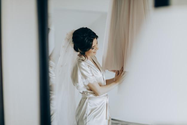 Ochtend van de bruid. bruidsprijzen. de bruid bewondert en raakt haar jurk aan Premium Foto