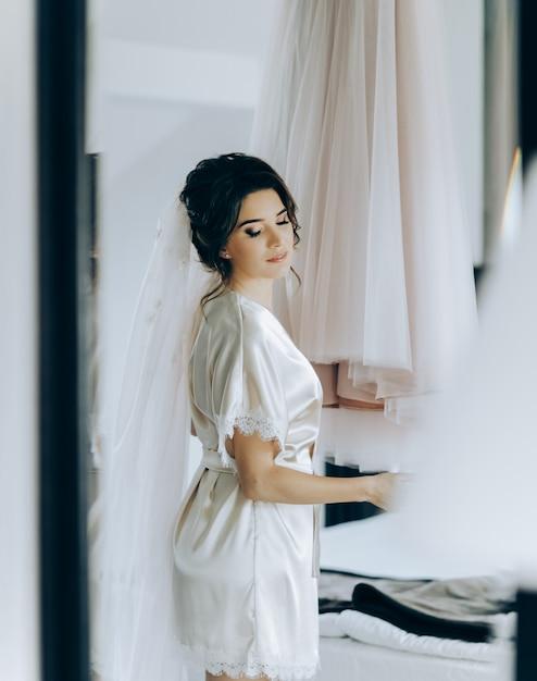 Ochtend van de bruid. de bruid bewondert en raakt haar jurk aan Premium Foto