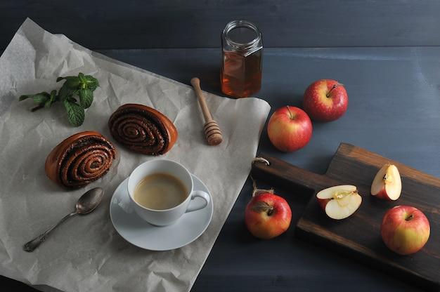 Ochtendkoffie met koffie en broodjes met maanzaad, appels en honing Premium Foto