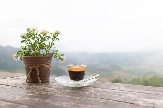 Ochtendkop van koffie en bloempot op de houten lijst met bergachtergrond Premium Foto