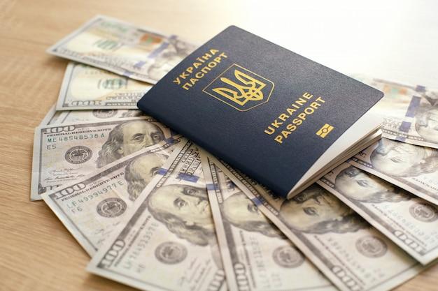 Oekraïens biometrisch paspoort en dollars. geld en documenten voor een reis naar het buitenland. documenten voor immigratie. Premium Foto