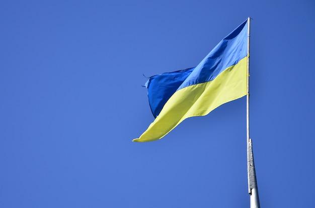 Oekraïense vlag tegen de blauwe wolkenloze hemel Premium Foto