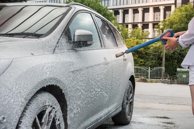 Oekraïense vrouw met schuimwaterpistool reinigt haar auto in dienst. schoonmaak concept Premium Foto