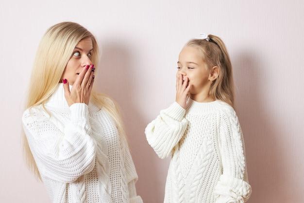 Oeps, omg. schattig klein meisje en haar jonge moeder beide in witte truien poseren geïsoleerd handen op de mond houden, verbaasd zijn over grote verkoopprijzen, gaan winkelen om kerstcadeautjes te kopen Gratis Foto
