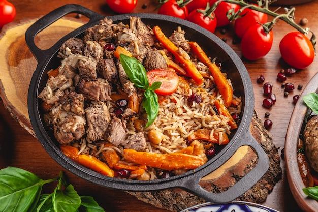 Oezbeekse pilaf in een gietijzeren pan. Premium Foto