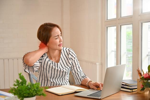 Office syndrome, vrouw aanraken masserende stijve nek om pijn te verlichten bij spieren die in verkeerde verkeerde houding werken. Premium Foto