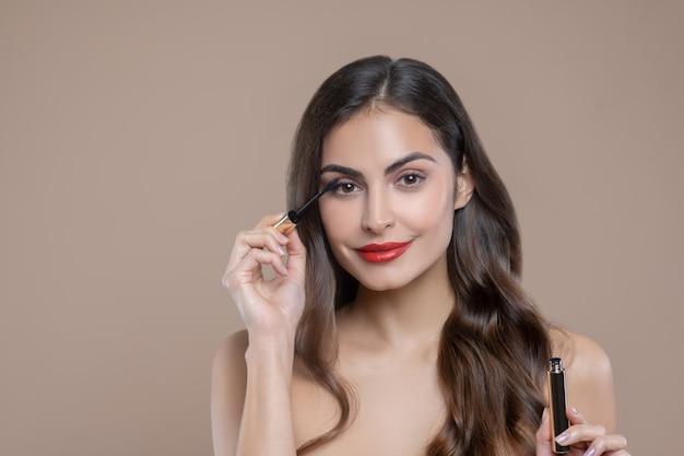 Ogen, wimpers. vrij donkerharige vrouw met blote schouders met rode lippen wimpers verven met mascara Premium Foto