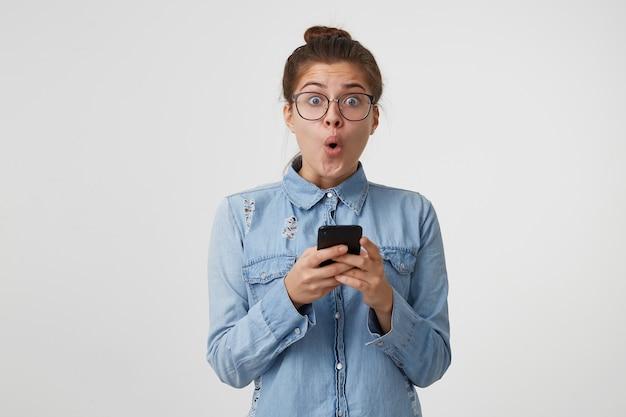 Oh mijn god, de vrouw houdt een smartphone in haar handen en kijkt verbaasd naar de camera met haar ogen wijd open en ronde mond Gratis Foto
