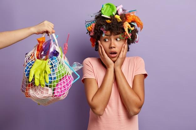 Oh nee, vervuil de natuur niet met plastic afval! ongelukkige etnische vrouw kijkt met geschokte uitdrukking naar zak vol met plastic afval, reinigt planeet, vormt binnen. dag van de aarde en vrijwilligerswerk concept Gratis Foto