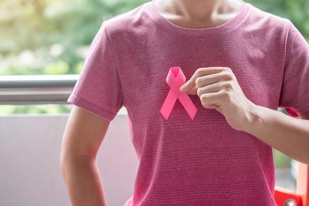 Oktober borstkanker maand, vrouw in roze t-shirt met hand met roze lint voor het ondersteunen van mensen die leven en ziekte. gezondheidszorg, internationale vrouwendag en werelddag voor kanker Premium Foto
