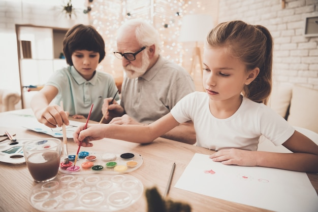 Old man paints with kids christmas with grandpa. Premium Foto