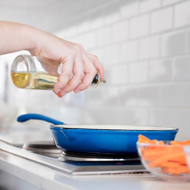 Olie op de braadpan serveren Gratis Foto