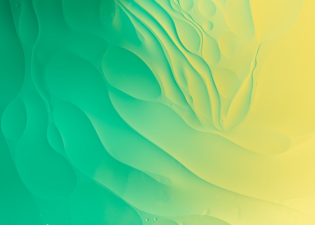 Olie op water macrofotografie van abstracte groene en gele kleurverloop achtergrond Premium Foto