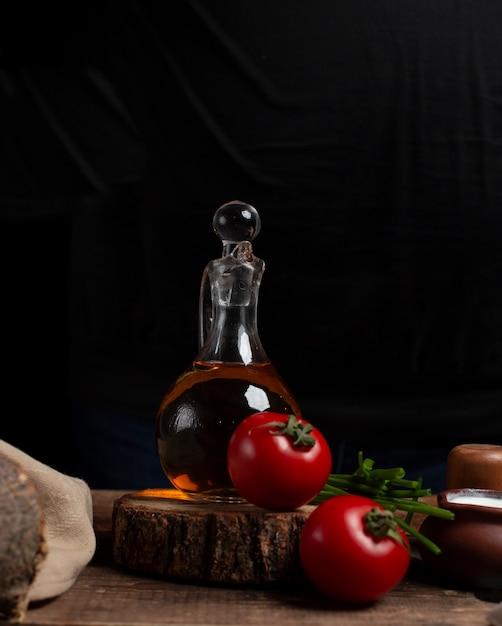 Oliefles, tomaten en kruiden op het stuk hout Gratis Foto