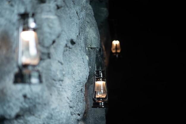 Olielamp opknoping op de stenen muur van de grot Premium Foto