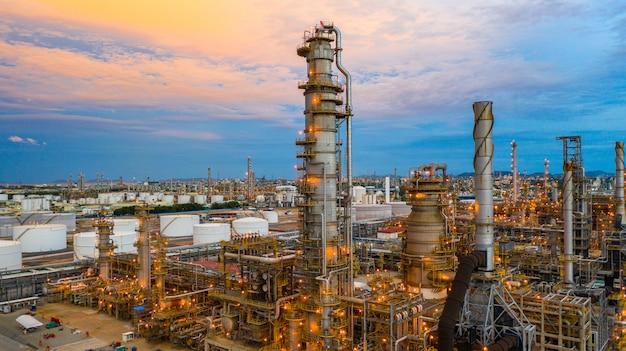 Olieraffinaderij bij schemering, luchtmenings petrochemische installatie en olieraffinaderijinstallatie achtergrond bij nacht, petrochemische olieraffinaderijfabriekinstallatie bij schemering. Premium Foto