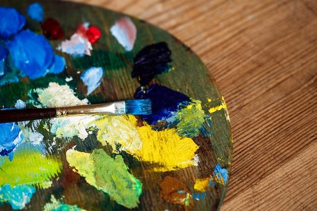Olieverf en penseel op palet over houten muur Gratis Foto