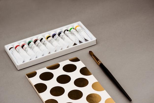 Olieverf, penseel en schetsboek op grijze tafel Gratis Foto