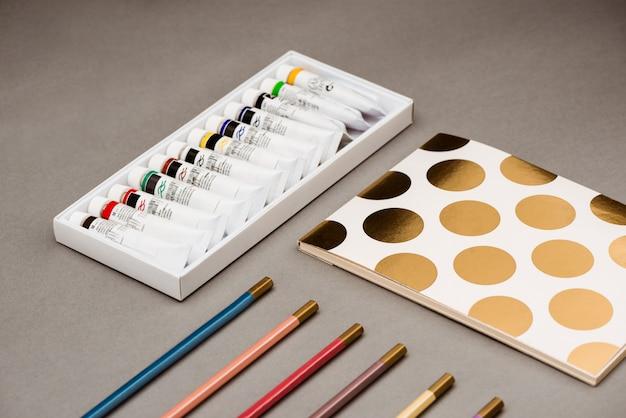 Olieverf, potloden en schetsboek op grijze tafel Gratis Foto