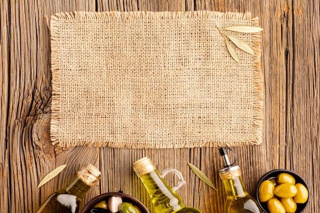 Olijfolieflessen met olijven en textielmodel Gratis Foto