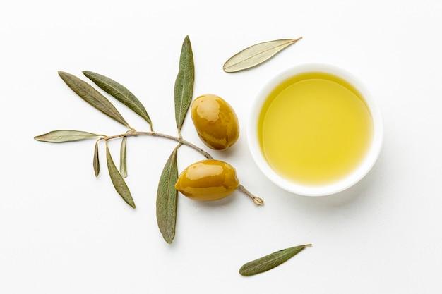 Olijfolieschotel met bladeren en gele olijven Gratis Foto