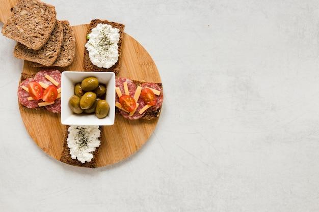 Olijven en broodjes op snijplank met kopie ruimte Gratis Foto