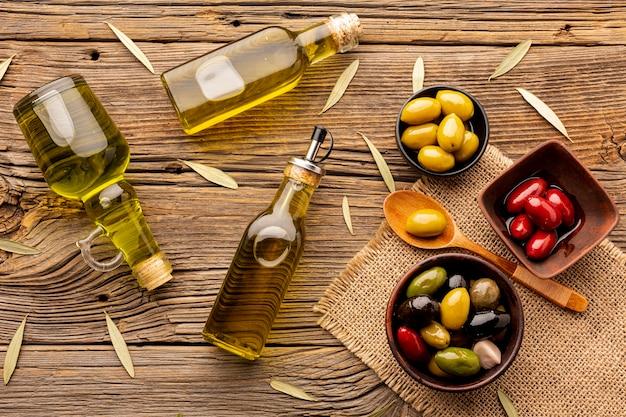 Olijven in kommen olieflessen en bladeren op textiel Gratis Foto