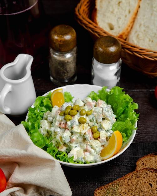 Olivier salade geserveerd met citroen Gratis Foto