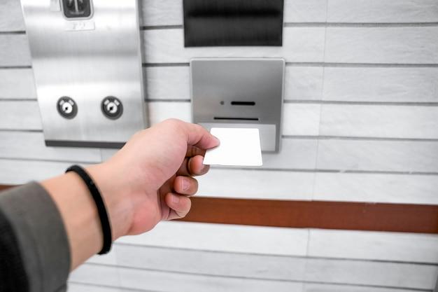 Om de toegangscontrole van de lift of lift te beveiligen, houdt de hand van een man een sleutelkaart omhoog om in de kaarthouder te steken om liftdeuren te ontgrendelen voordat deze omhoog of omlaag gaat. Premium Foto