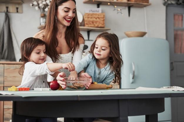Om deze heerlijke dingen te bereiken. de jonge mooie vrouw geeft de koekjes terwijl zij dichtbij de lijst met speelgoed zitten Premium Foto