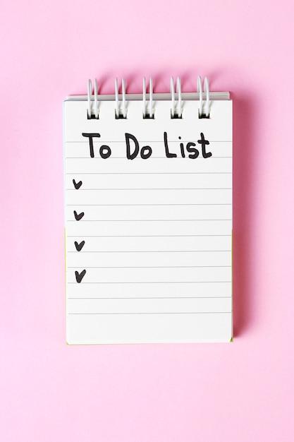 Om lijst in notitieboekje op roze achtergrond, exemplaarruimte, planningsconcept te doen Premium Foto