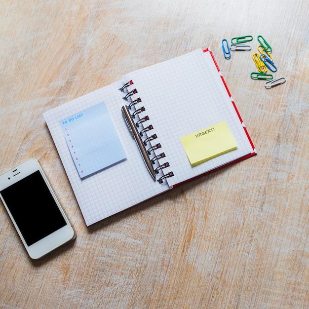 Om lijstblocnote en dringende kleverige nota op geruite laptop met smartphone en paperclip te doen Gratis Foto