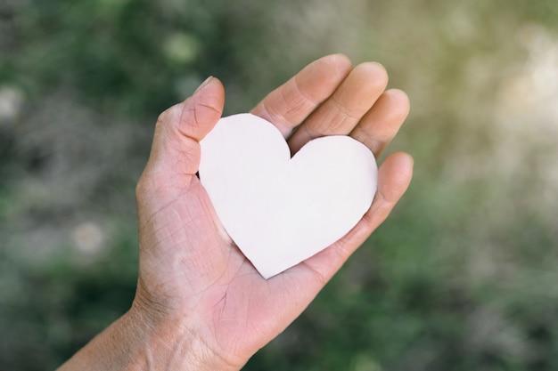 Oma's hand houdt een hart vast Premium Foto