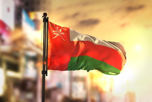 Oman vlag tegen stad wazige achtergrond bij zonsopgang achtergrondverlichting Premium Foto