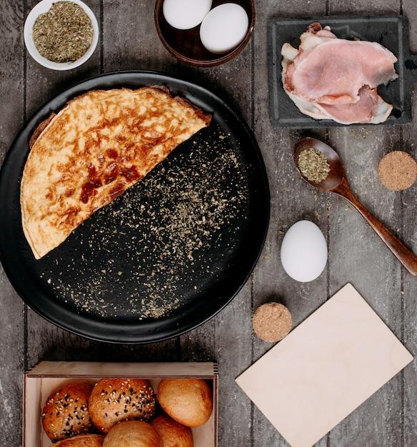 Omelet in de pan en rauwe bacon aan de zijkant Gratis Foto