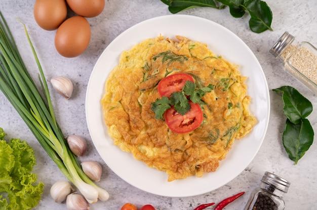 Omelet in een wit bord gegarneerd met tomaten en koriander. Gratis Foto